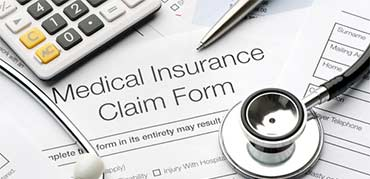 Image of random objects on top of a Medical Insurance Claim Form